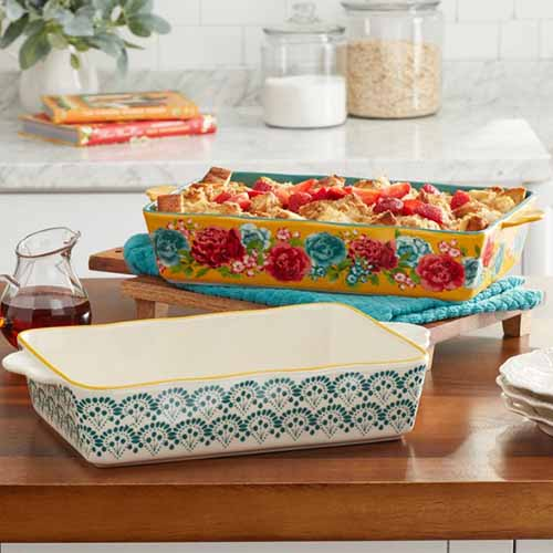 A close up of baking dishes set on a wooden surface with a kitchen countertop in the background.