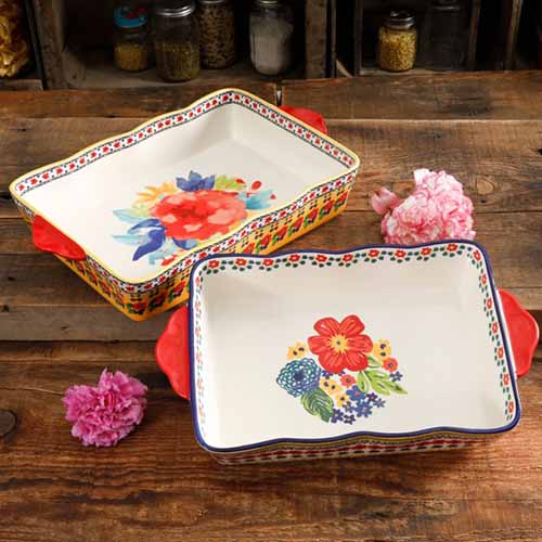 A close up square image of two baking dishes set on a wooden surface.