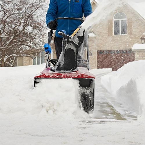 A close up square image of a homeowner clearing a driveway using the Toro Power Clear 721 QZE with a stone house in soft focus in the background.
