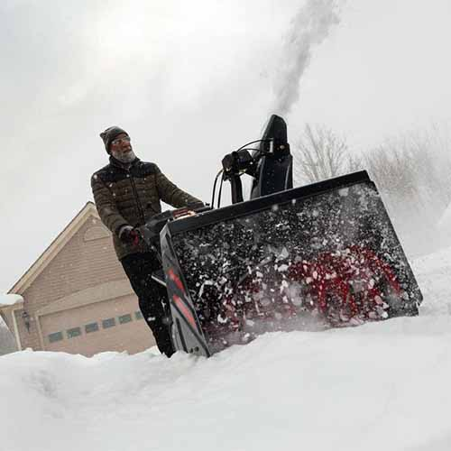 A close up square image of a man pushing the Troy-Bilt Arctic Storm 30 to clear a driveway, pictured with a house in the background.
