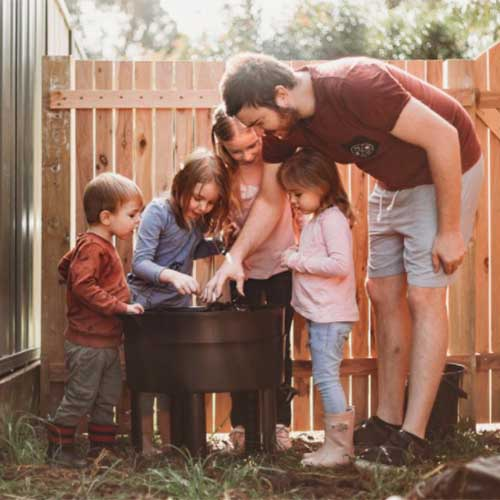 A close up square image of a family attending to a worm farm in a black plastic container with a wooden fence in the background.