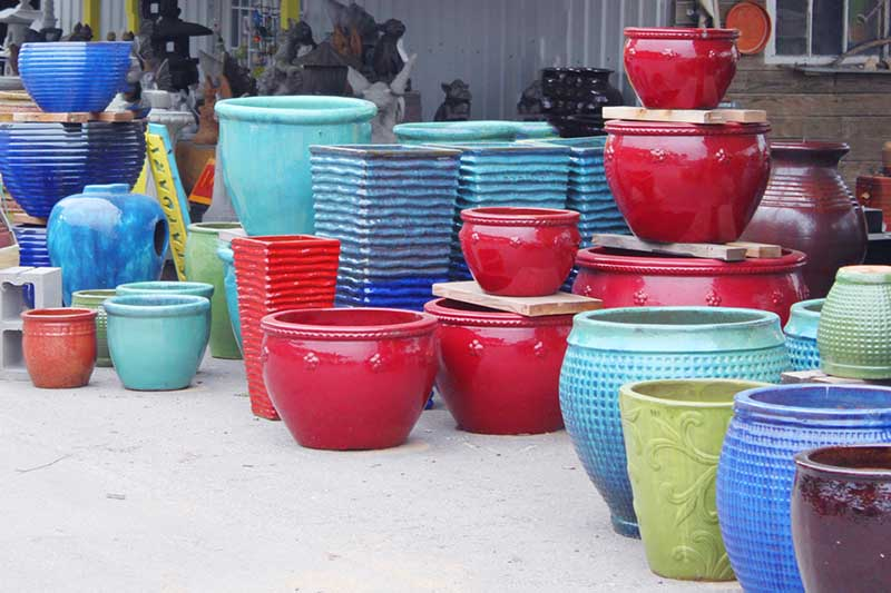 A horizontal image of large pots in different shapes, sizes, and colors for sale at a garden center.