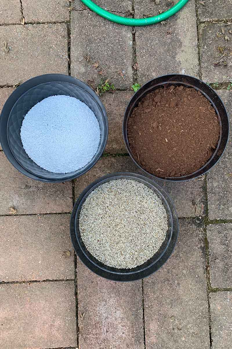 A top down vertical image of three pots containing different elements of potting mediums set on a brick surface.