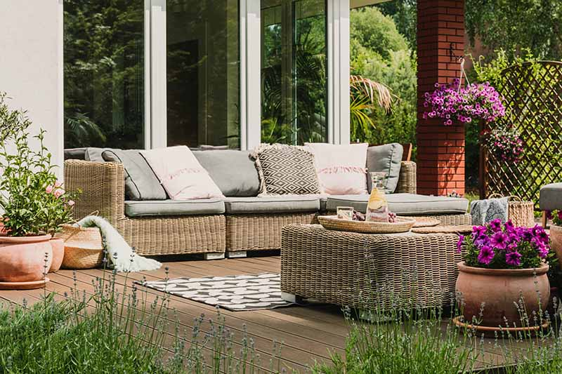 A horizontal image of a deck scene with wicker furniture, rugs, and a variety of plants.