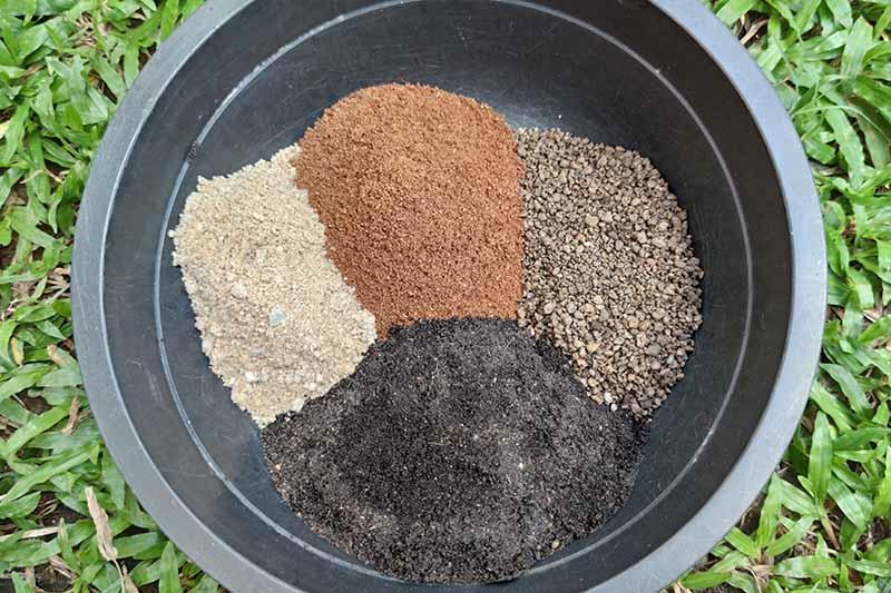 Una imagen horizontal en primer plano de una maceta negra que contiene varios medios de plantación para mezclarlos como una mezcla para macetas, colocada sobre una superficie cubierta de hierba.