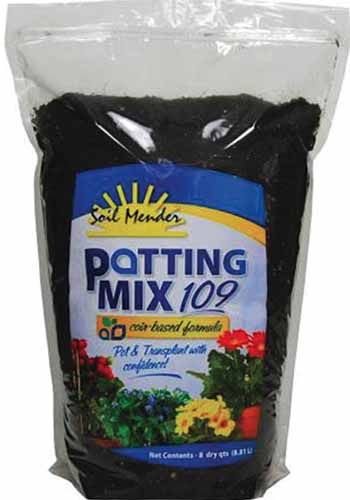 A close up vertical image of the packaging of Soil Mender Potting Mix for indoor plants pictured on a white background.