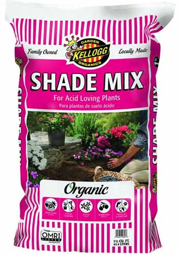 A close up vertical image of the packaging of Shade Mix potting soil for acid-loving plants pictured on a white background.