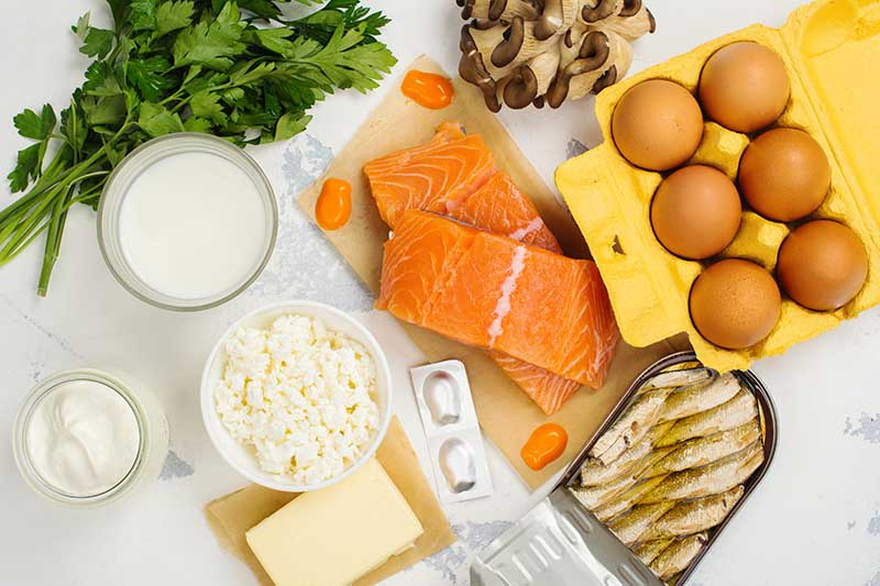 A top down horizontal image of various foods, salmon, eggs, milk, cheese, herbs, and mushrooms set on a white surface.