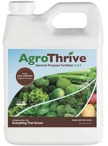 A close up square image of a plastic bottle of AgroThrive, a general purpose fertilizer for houseplants.