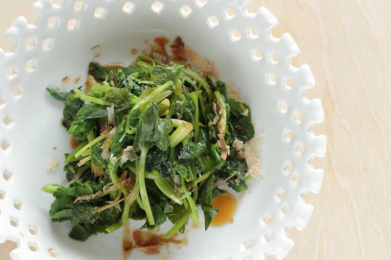A close up horizontal image of a decorative white bowl with cooked mitsuba leaves and stalks.