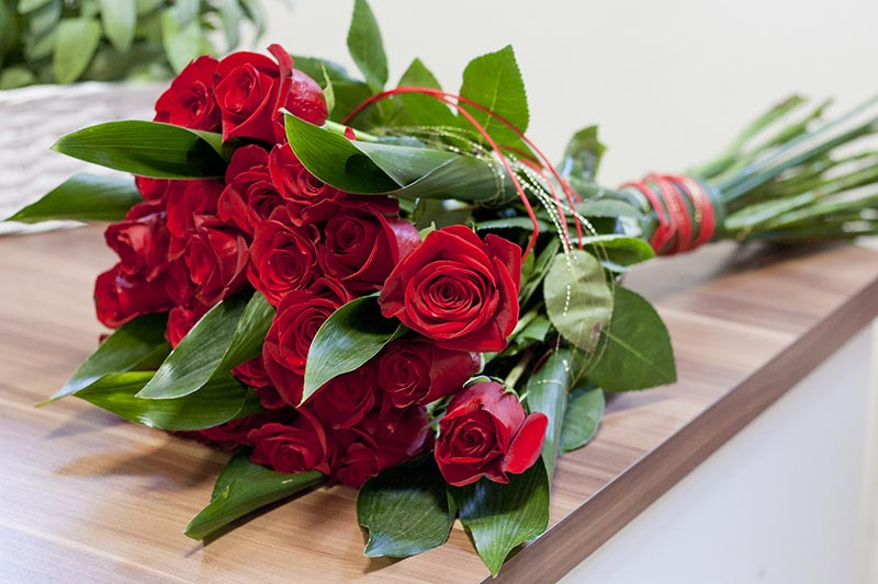 A close up horizontal image of a bouquet of red flowers with decorative ribbons set on a wooden surface.