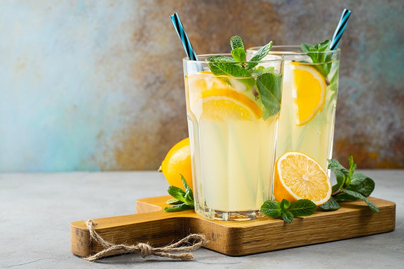 A close up horizontal image of two glasses of mojito cocktails set on a wooden chopping board, surrounded by herbs and slices of orange.