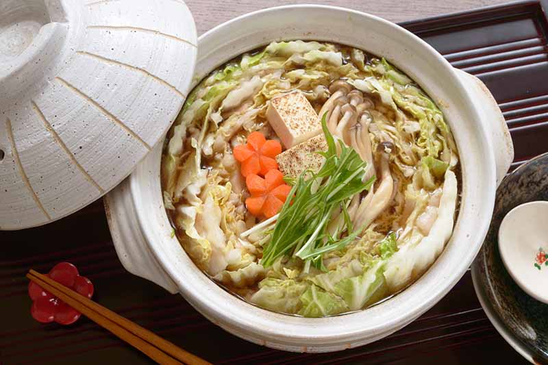 A close up horizontal image of a cabbage, tofu, and mitsuba stew in a ceramic pot set on a black surface.
