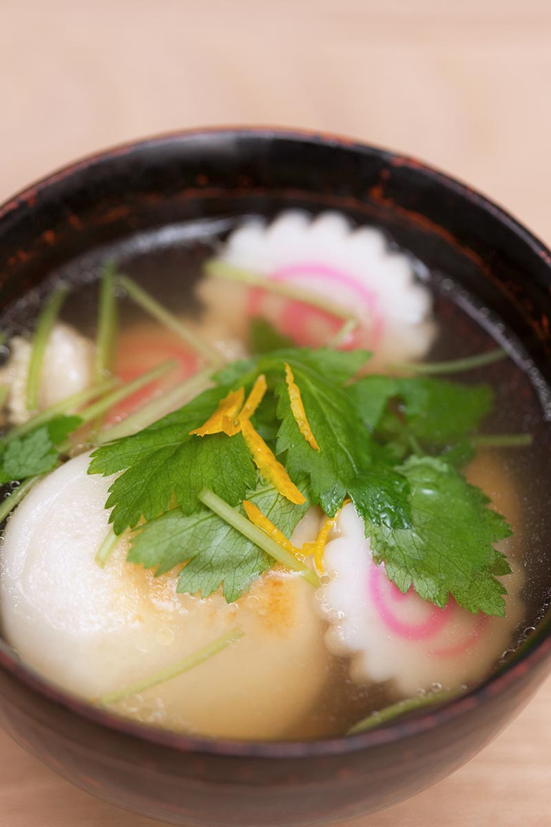 A close up vertical image of a clear soup with dumplings garnished with mitsuba pictured on a soft focus background.