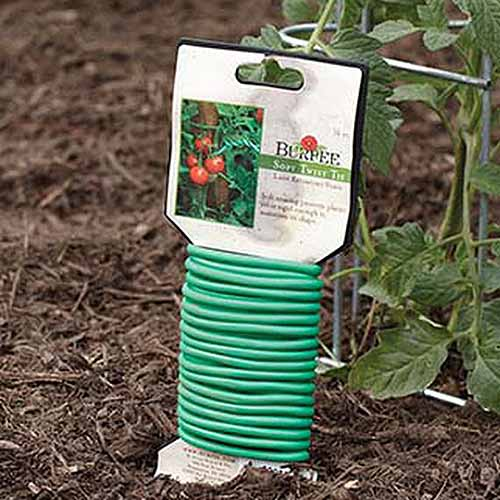 A close up square image of a package of twist ties for supporting climbing plants set on soil in the garden.