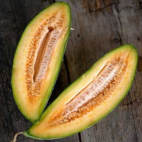 A close up square image of a Cucumis melo 'Banana' cut in half and set on a wooden surface.