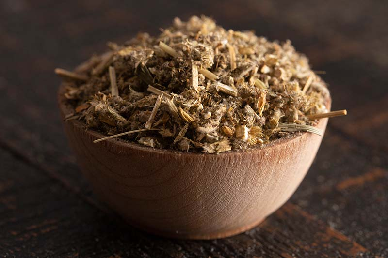 A close up horizontal image of a small wooden bowl containing dried horehound (Marrubium vulgare) on a wooden surface.