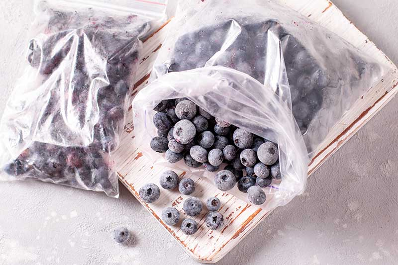 A close up horizontal image of two plastic bags filled with frozen fruits set on a wooden surface.