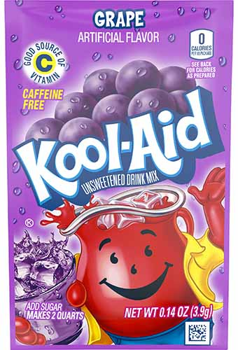 A close up vertical image of the horrible garish packaging of Grape Kool-Aid.