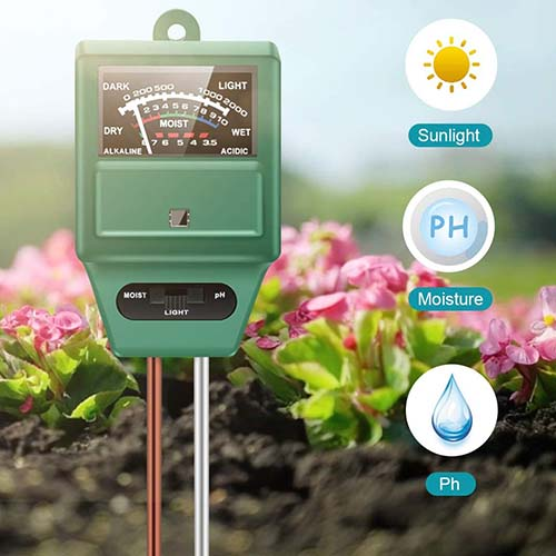 A close up square image of a Hayi hygrometer with soil and flowers in soft focus in the background and icons to the left of the frame.
