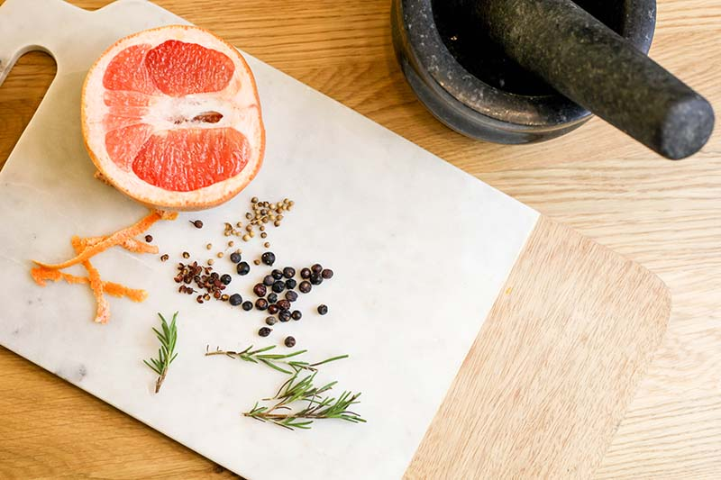 A close up horizontal image of the ingredients for making gin, including berries, half a grapefruit, and herbs set on a wooden surface.