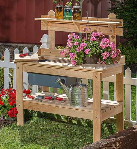 A close up square image of a sturdy cypress potting table set outside on a lawn with a white picket fence in the background.