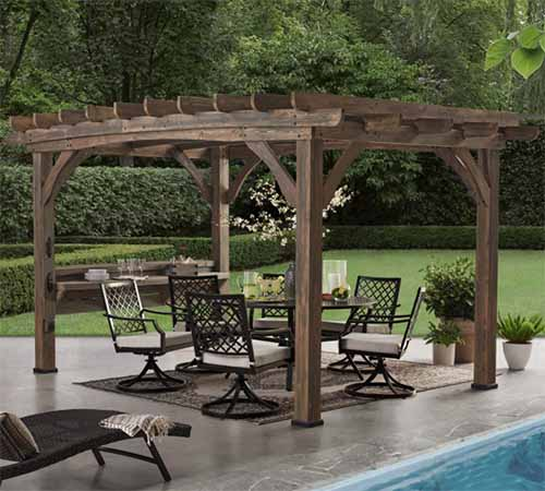 A square image of a cedar pergola set up beside a swimming pool with chairs and a table under it and a garden scene in the background.