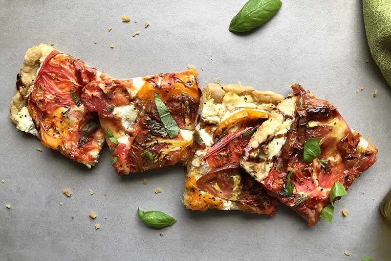 A close up horizontal image of slices of einkorn pizza set on a light gray surface with basil scattered around.