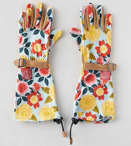 A close up square image of long-armed gardening gloves in a floral pattern set on a light gray surface.