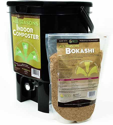 A close up square image of an indoor composter in black plastic with a bag of bokashi mix to the right of the frame isolated on a white background.