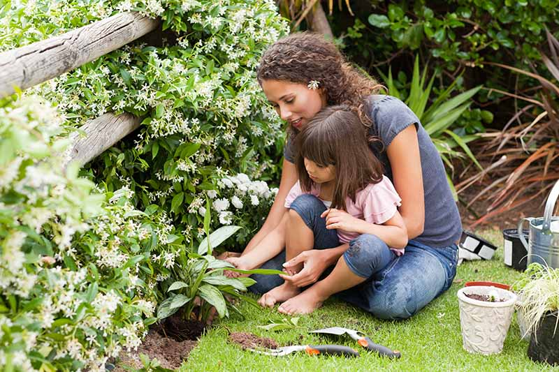 A horizontal image of a mother and child working together in the garden.