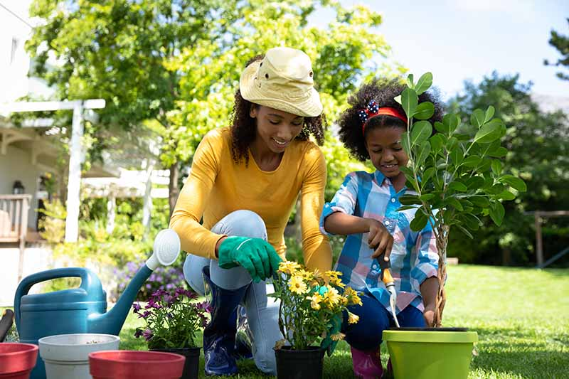 A horizontal image of a woman and child potting up flowers in the garden pictured in bright sunshine.