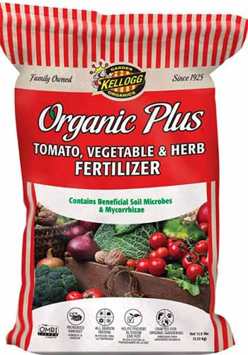 A close up vertical image of the packaging of Organic Plus Tomato, Vegetable, and Herb Fertilizer isolated on a white background.