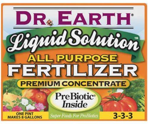 A close up horizontal image of Dr Earth Liquid Solution All Purpose Fertilizer isolated on a white background.