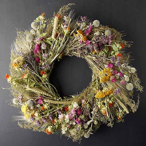 A close up square image of a dried garden wreath set on a dark gray background.