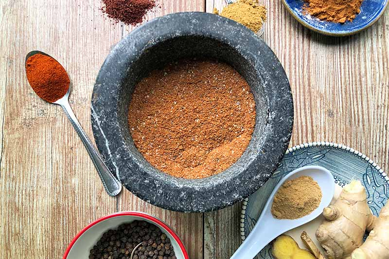 A close up top down horizontal image of a mortar filled with ras-el-hanout spice blend set on a wooden surface with individual spices surrounding.