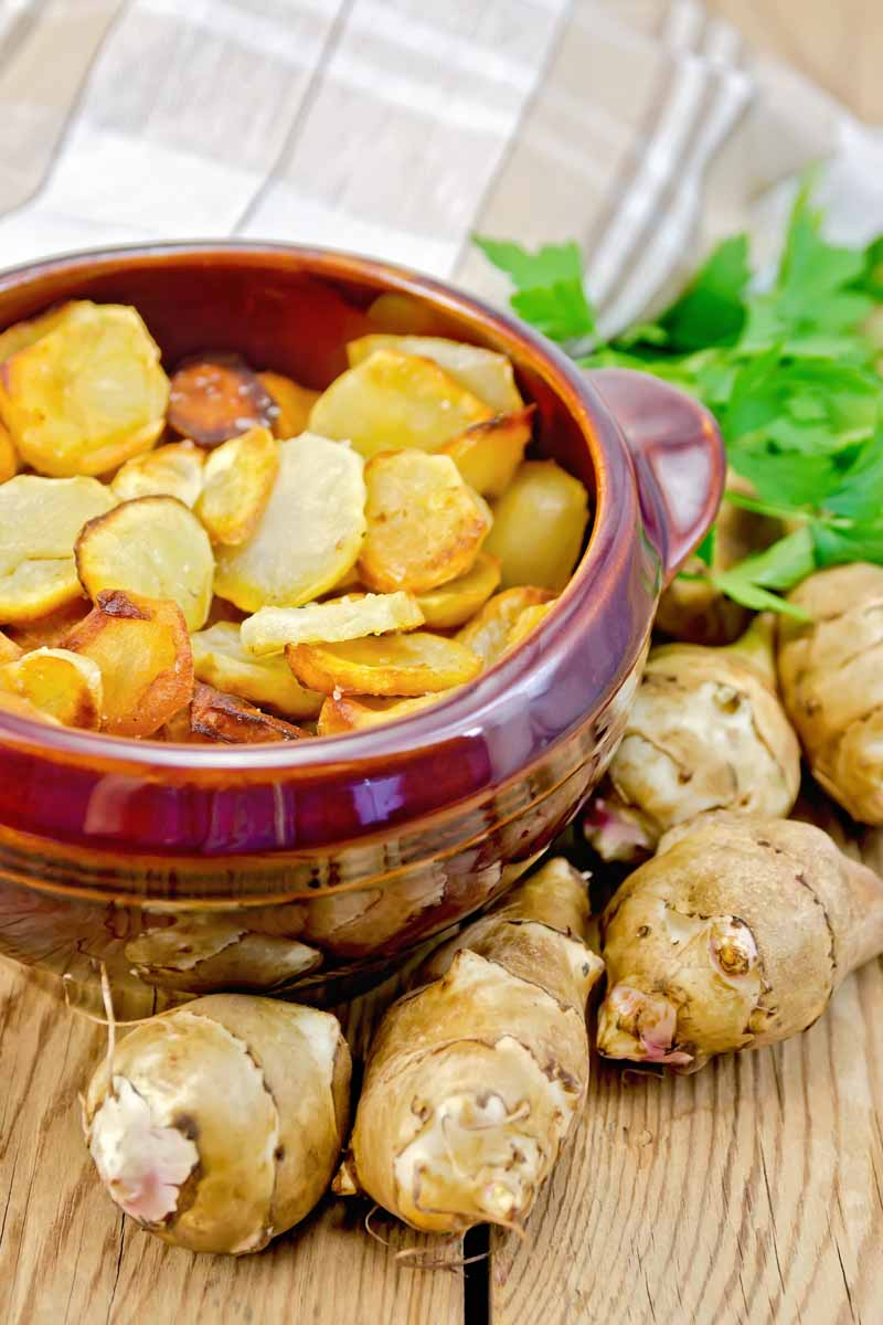 A clay bowl full of roasted Jerusalem artichokes in a clay bowl with fresh tubers sitting to the right.