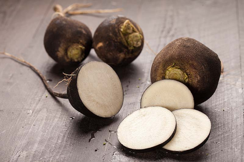 A close up horizontal image of sliced and whole 'Round Black Spanish' radishes set on a wooden surface.