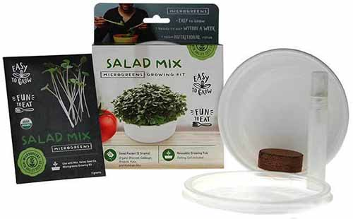 A close up horizontal image of a microgreens starter kit and a packet of Salad Mix seeds isolated on a white background.