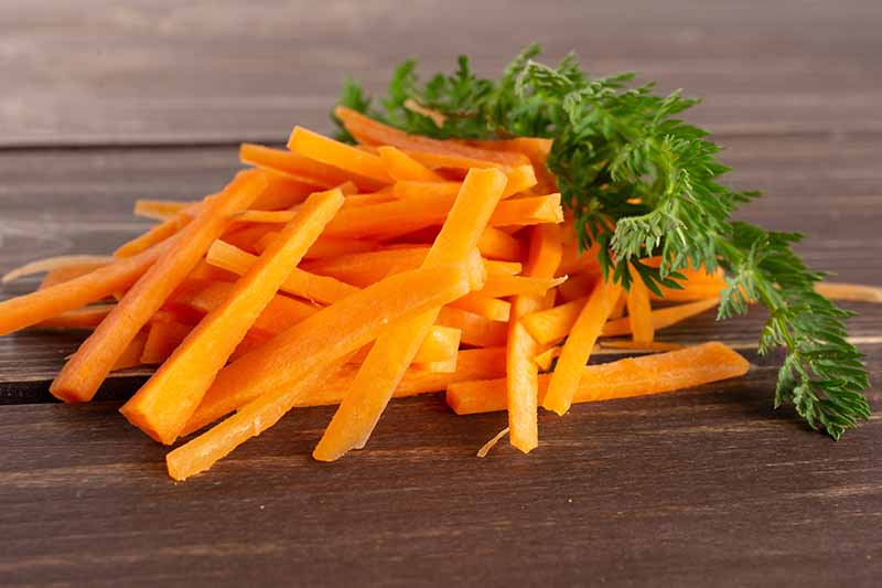 A close up horizontal image of pieces of fresh carrot cut into thin slices with greens set on a wooden surface.