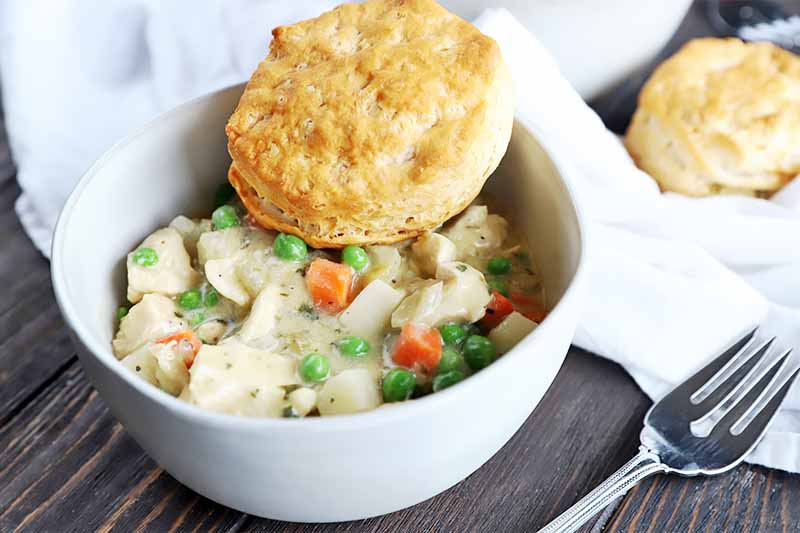 A close up horizontal image of a white bowl with freshly prepared chicken pot pie set on a wooden surface with a fork and white cloth to the left of the frame.