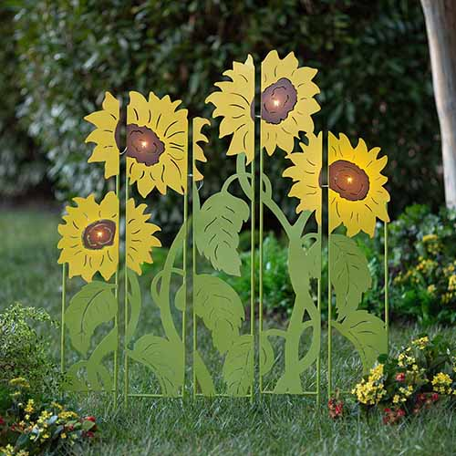 A close up square image of a metal sunflower lighted garden panel set outdoors on the lawn with plants in soft focus in the background.