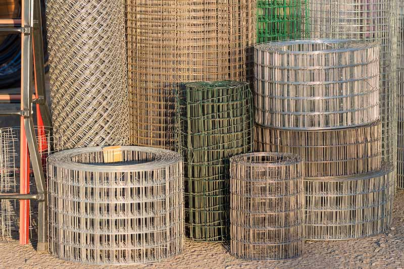 A close up horizontal image of rolls of wire metal fencing in a garden center.