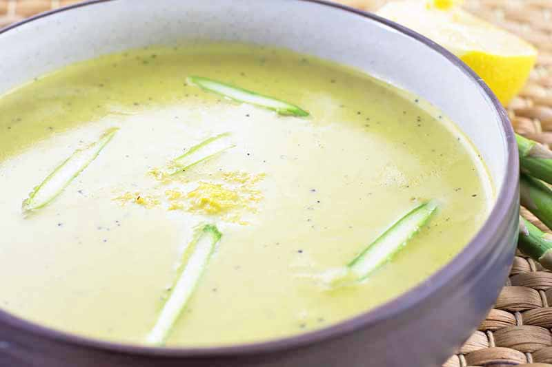 A close up horizontal image of freshly prepared cream of asparagus soup set on a wicker tablemat.