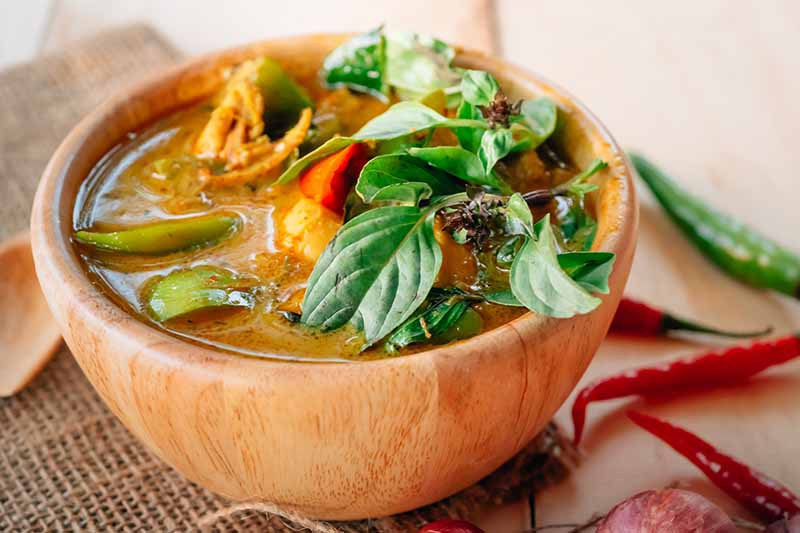 A close up horizontal image of a wooden bowl with a freshly made Thai curry, garnished with basil set on a wooden surface with hot peppers scattered around.