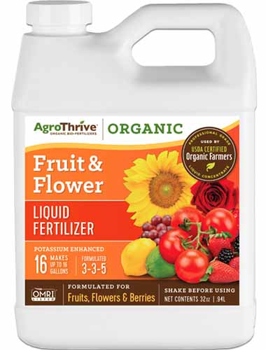 A close up square image of a plastic bottle of AgroThrive Organic Fruit and Flower Liquid Fertilizer isolated on a white background.