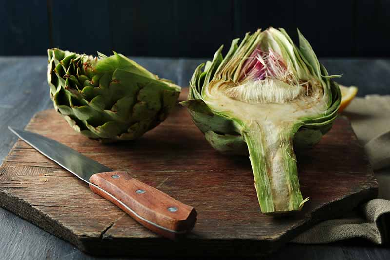 A close up horizontal image of a globe artichoke that has been cut in half on a wooden chopping board, with a knife to the left of the frame.