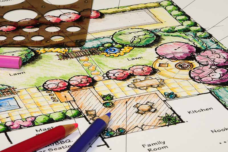 A horizontal image of a hand drawn garden design with colored pencils at the bottom of the frame.