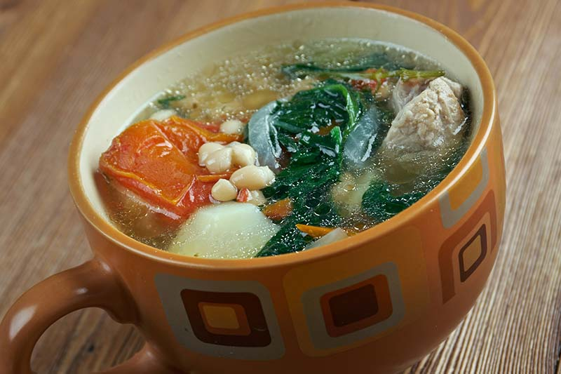 A close up horizontal image of a small cut of traditional caldo Gallego, a Spanish broth.