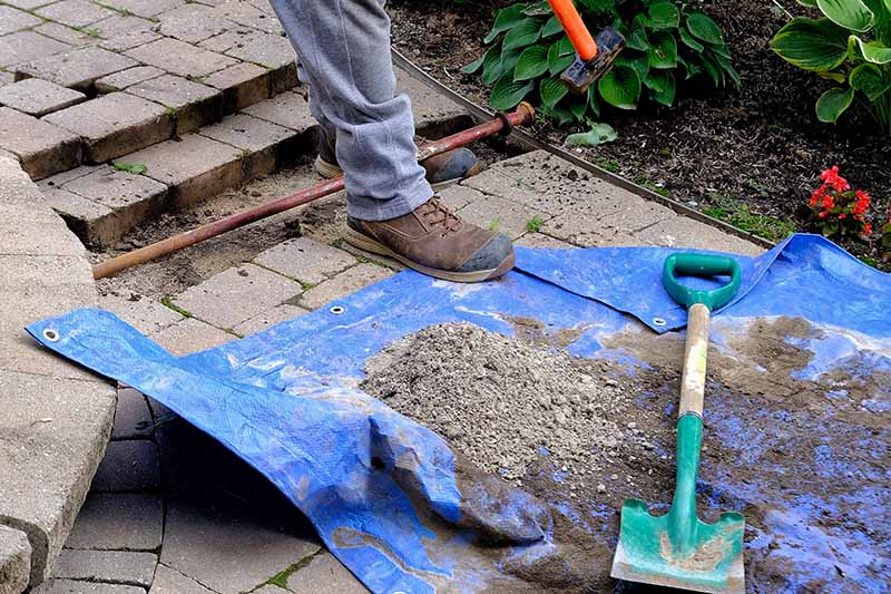 A close up horizontal image of a gardener working on a garden border with a tarp and spade to the bottom of the frame.